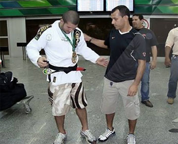 Rodolfo receiving his black belt at the airport.